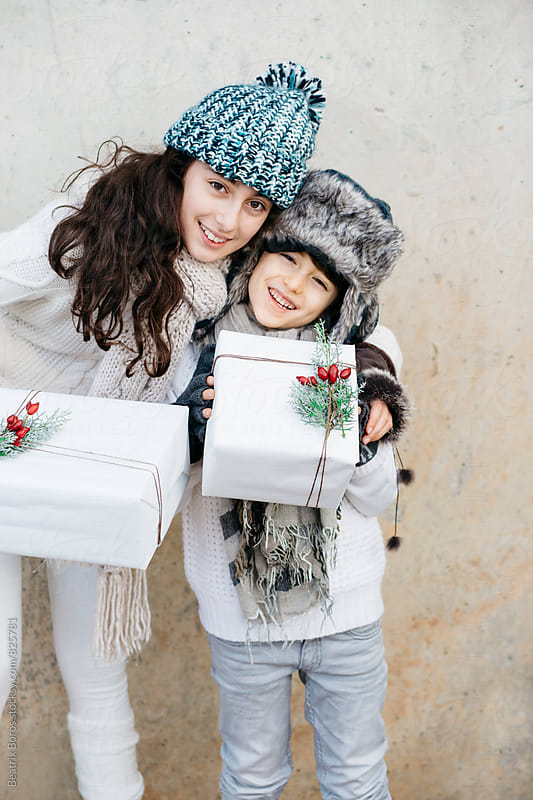 Two kids holding two Christmas boxes happily looking at camera  by Beatrix Boros for Stocksy United