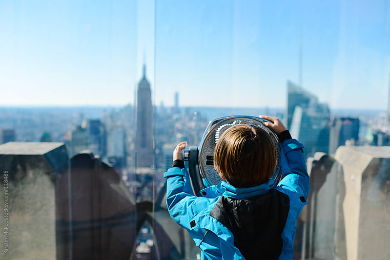 Boy looking out over Manhattan. by Kirstin Mckee for Stocksy United