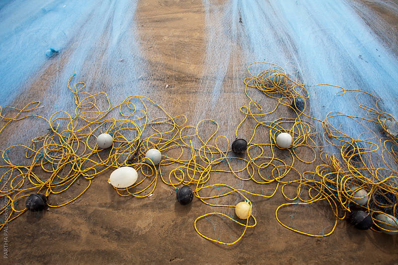 Fishing net lying on beach, close view by PARTHA PAL for Stocksy United