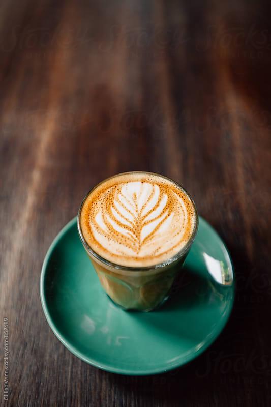 flat white coffee with rosetta latte art by Gillian Vann for Stocksy United