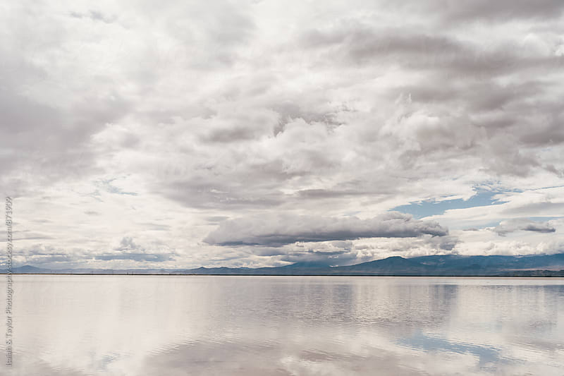 Cloudy sky reflecting on lake by Isaiah & Taylor Photography for Stocksy United