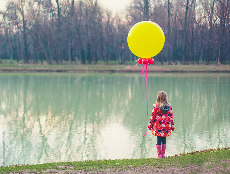 Girl With a Balloon Standing by the River by Lumina for Stocksy United