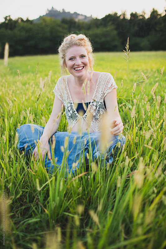 Happy pregnant woman sitting in a meadow by michela ravasio for Stocksy United