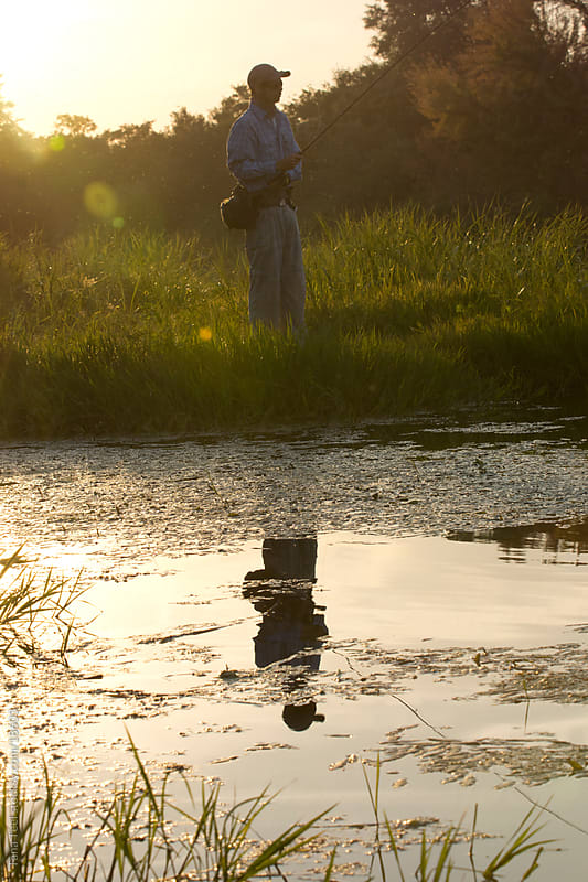The reflection of a young man fly fishing along the river.  by Tana Teel for Stocksy United