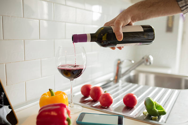 Man Pooring  a Red Wine Glass While is Cooking by HEX. for Stocksy United