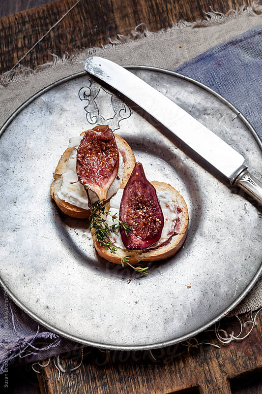 Roasted figs on goat cheese  crostini by Susan Brooks-Dammann for Stocksy United
