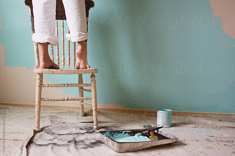 Young woman stands on tip toe on a chair while painting by Tana Teel for Stocksy United