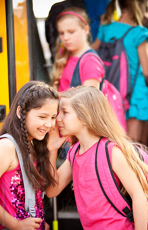 School Bus: Girls Gossip About Another Girl by Sean Locke for Stocksy United