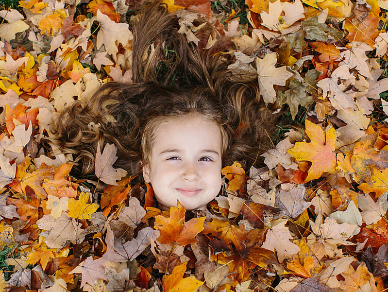 Cute girl with big cheeks cover in leafs  by Jakob for Stocksy United