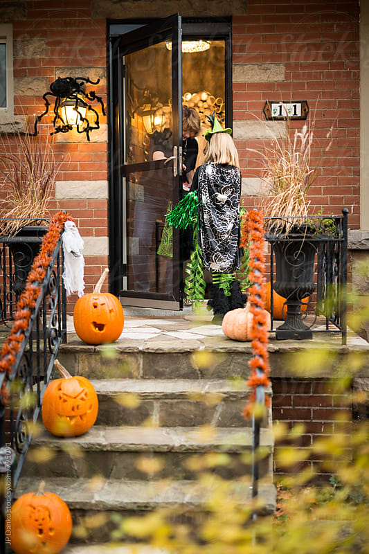 Girl Dressed as A Witch Getting Candy At Door Trick or Treat on Halloween by JP Danko for Stocksy United