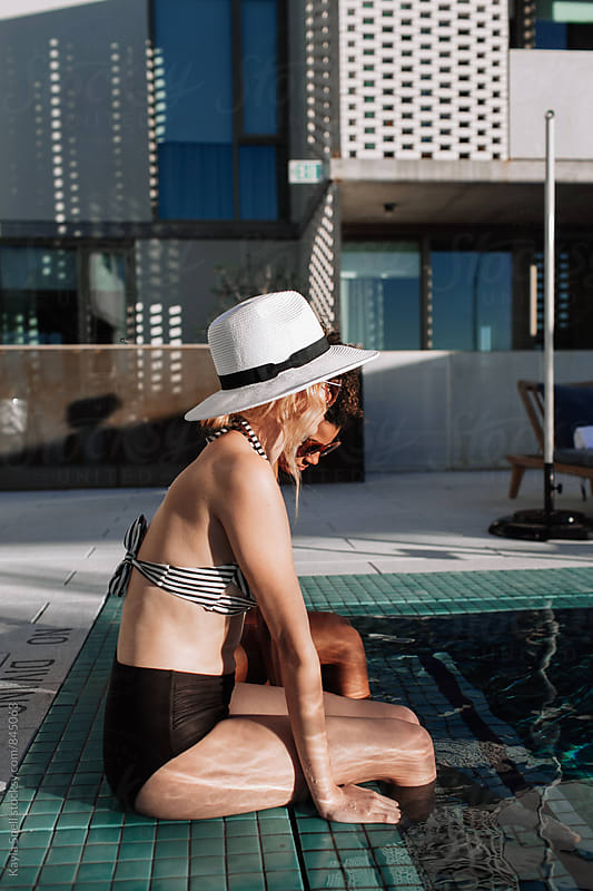 women by the pool by Kayla Snell for Stocksy United