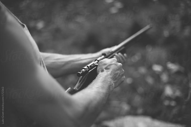 Man cocking rifle by Luke Gram for Stocksy United