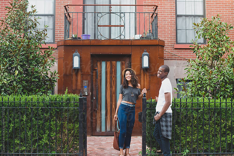 Couple standing in front of apartment building by Lauren Naefe for Stocksy United