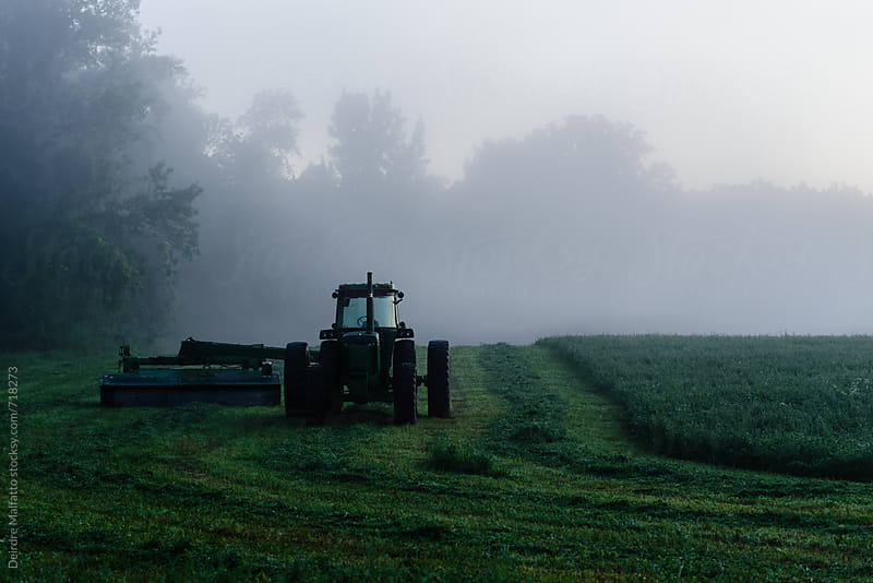 tractor hiding in the early morning mist by Deirdre Malfatto for Stocksy United