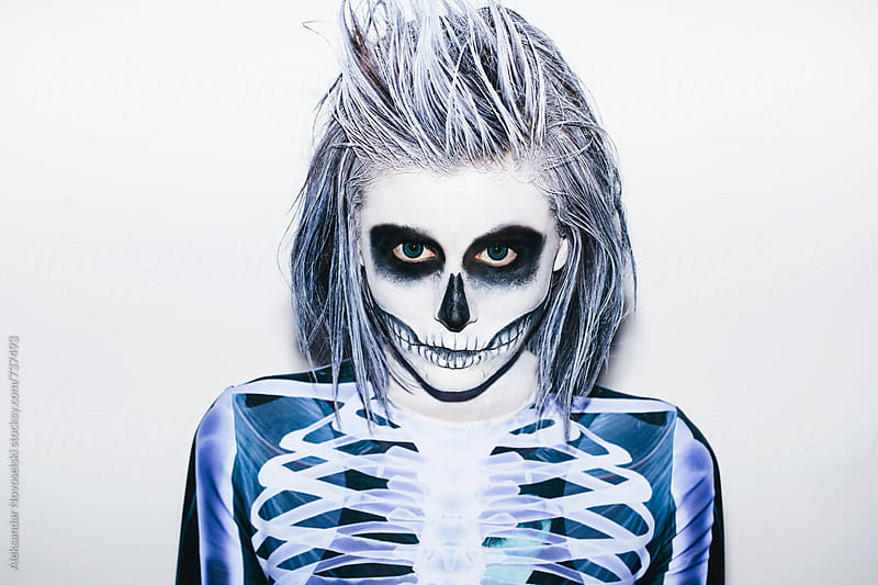 Portrait of a young woman with halloween make up and skeleton costume by Aleksandar Novoselski for Stocksy United