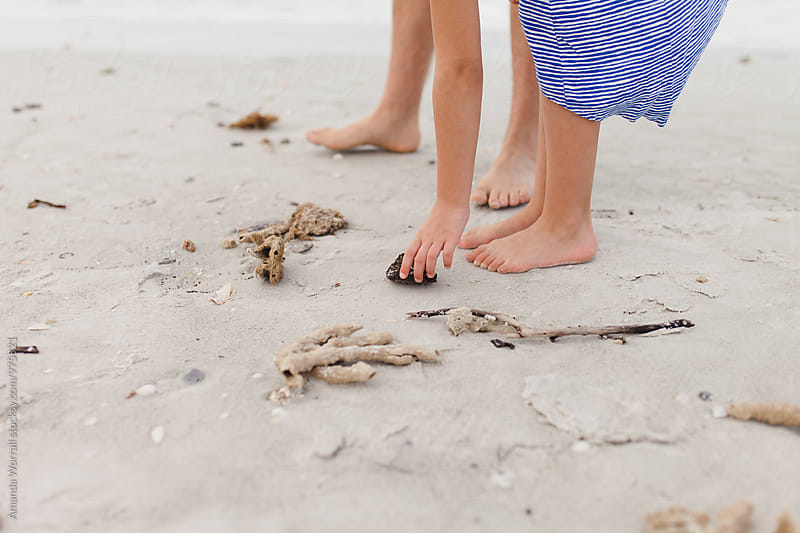 Children's hands and feet in sand, picking up beach treasures by Amanda Worrall for Stocksy United