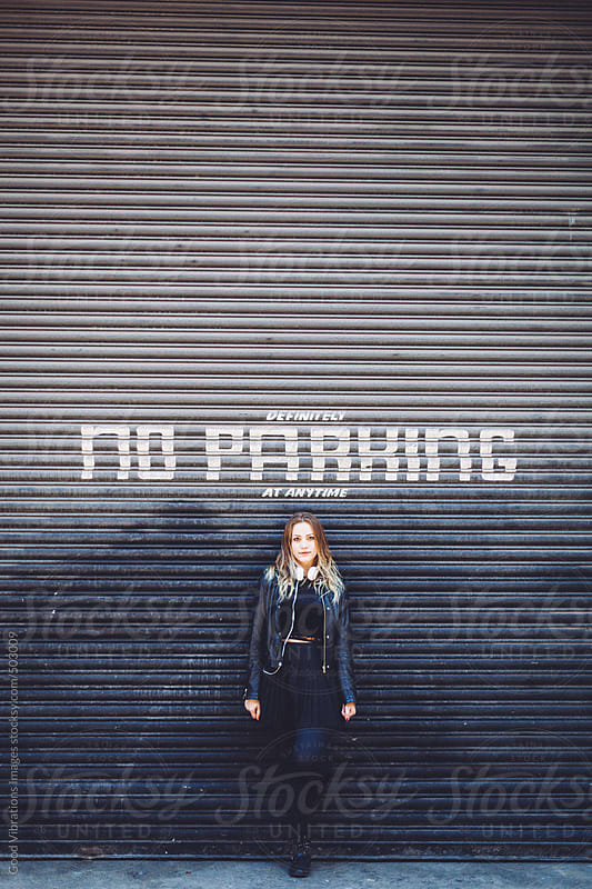 Woman standing in front of a No Parking sign by Good Vibrations Images for Stocksy United