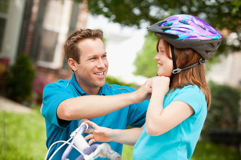 Father: Helping Child Put on Bike Helmet by Sean Locke for Stocksy United