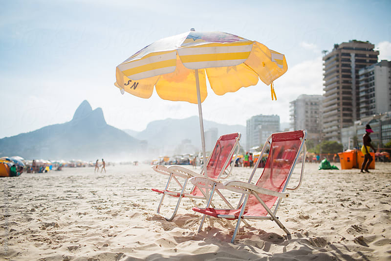two beach chairs sitting alone in Ipanema Beach  by HOWL for Stocksy United