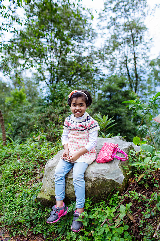 Little girl sits on a rock in the forest and smiling by Saptak Ganguly for Stocksy United