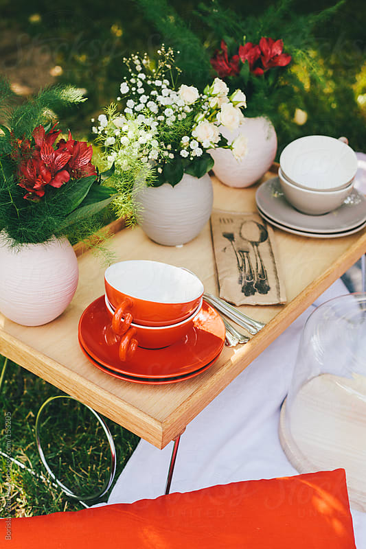 Cups on wooden tray out in the garden decorated with a lot of flowers. by Borislav Zhuykov for Stocksy United