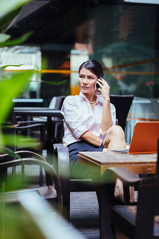 Attractive business woman using her cellphone by michela ravasio for Stocksy United
