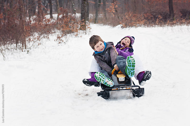 Young girl and boy having a great time sledging by Lea Csontos for Stocksy United