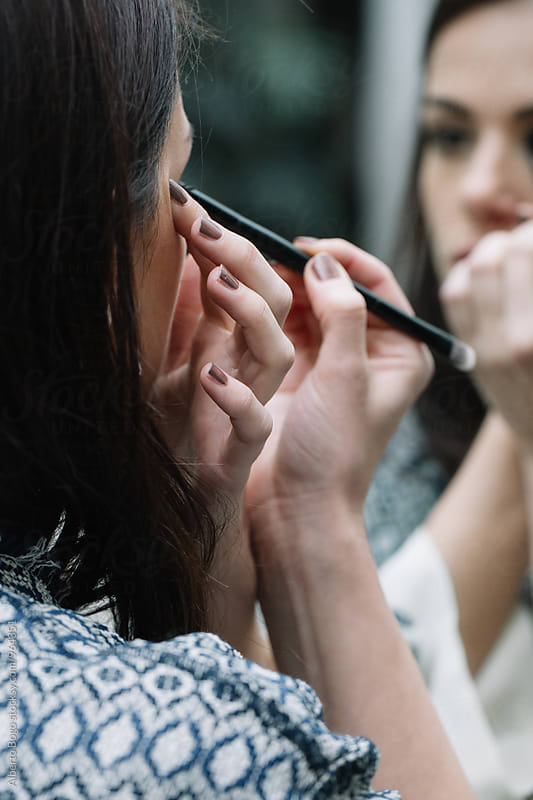 Young dark-haired woman doing make-up by Alberto Bogo for Stocksy United