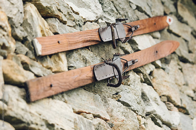 wooden old skis in the stone wall by Jordi Rulló for Stocksy United