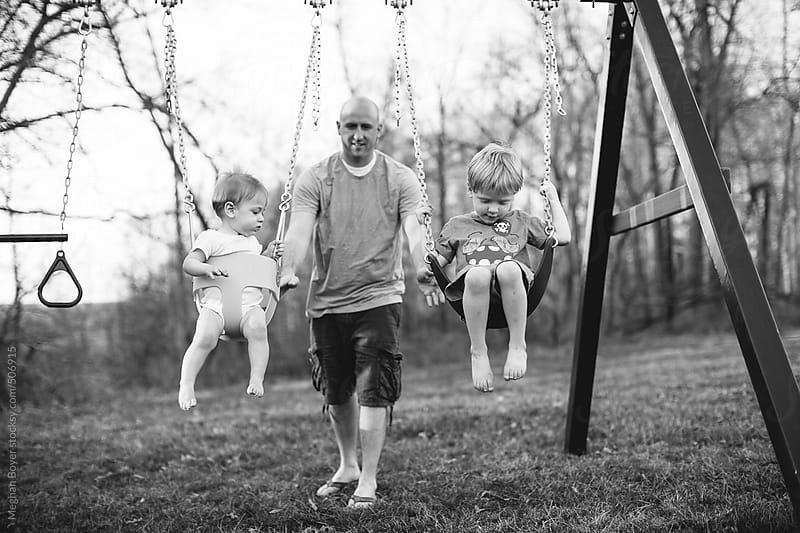 father pushing his sons on a swing  by Meghan Boyer for Stocksy United