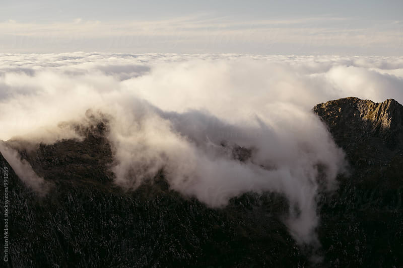 Clouds drift over the top of a far out mountain ridge at sunset by Christian McLeod Photography for Stocksy United