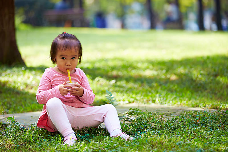 little asian girl in the park by Bo Bo for Stocksy United