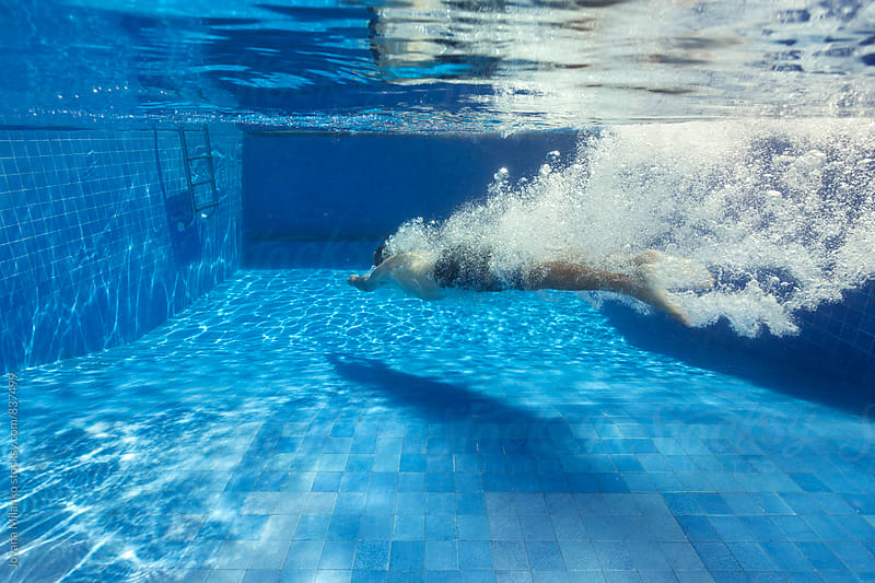 Man underwater after a headplunge in the pool by Jovana Milanko for Stocksy United