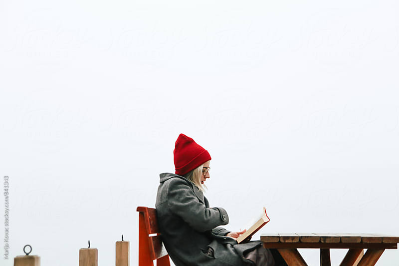Girl reading a book outdoor, wearing red cap - horizontal by Marija Kovac for Stocksy United