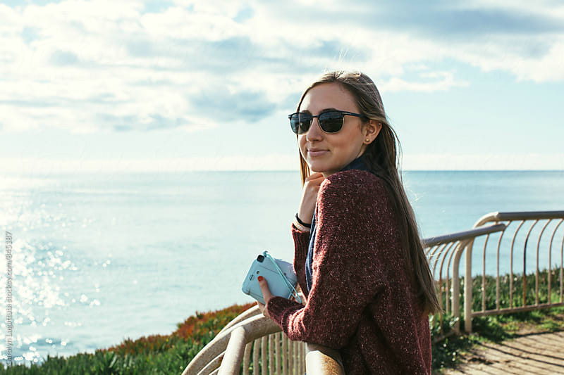 Beautiful teenage girl by the ocean wearing sunglasses by Carolyn Lagattuta for Stocksy United