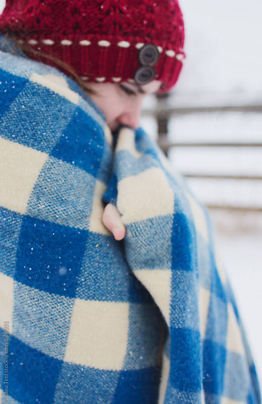 young woman wrapped in wool plaid blanket in snow by Tana Teel for Stocksy United