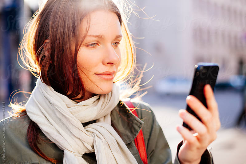 Young woman using smartphone by Aleksandra Kovac for Stocksy United