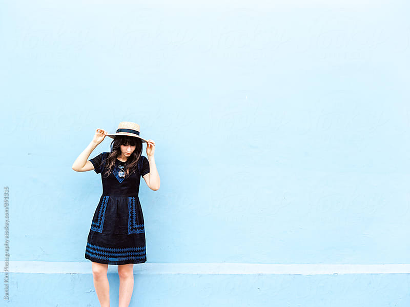 Woman standing in front of blue wall by Daniel Kim Photography for Stocksy United