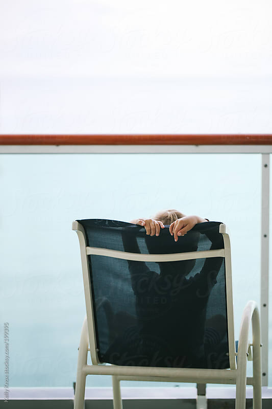 child relaxes on a deck overlooking the ocean by Kelly Knox for Stocksy United