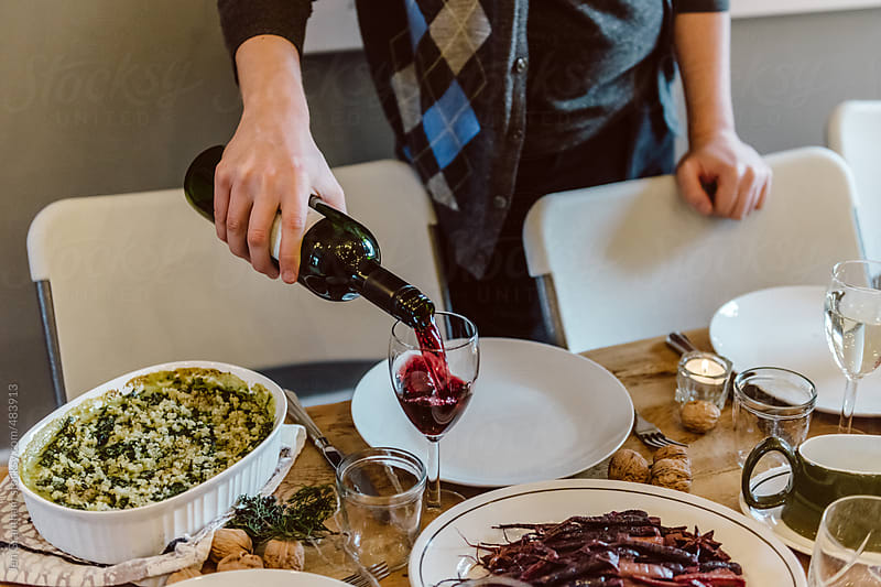 Pouring wine for Christmas dinner by Jen Grantham for Stocksy United