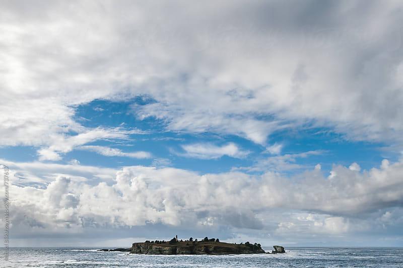 Small rocky island under cumulus clouds by Mihael Blikshteyn for Stocksy United