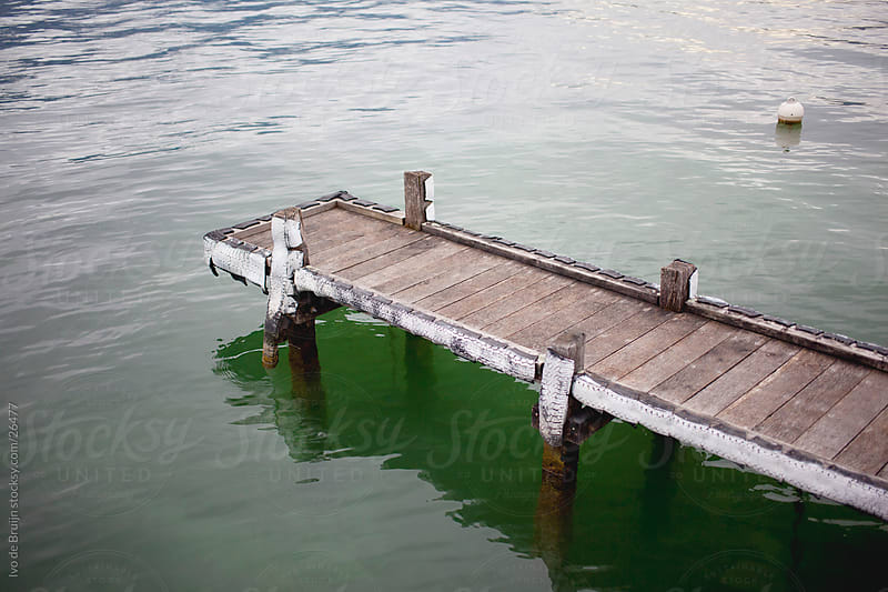 A small wooden pier or wharf in a lake by Ivo de Bruijn for Stocksy United