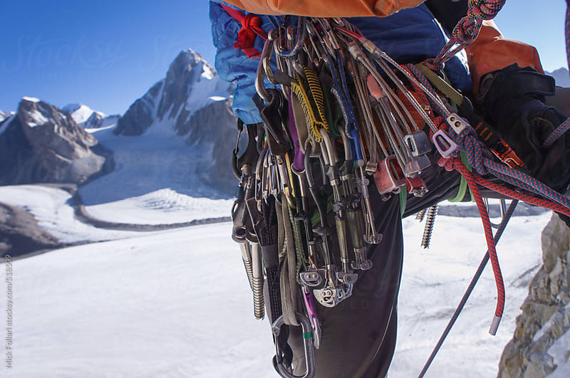 Traditional ice and rock climbing gear on a harness in the alpine mountains with glacier behind by Mick Follari for Stocksy United