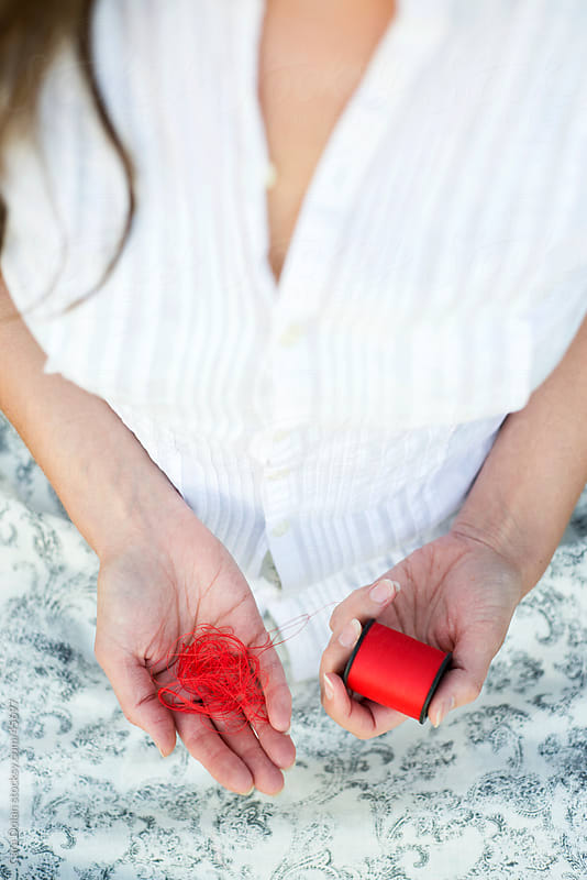 Woman's hands holding a spool of red sewing thread by Cara Slifka for Stocksy United