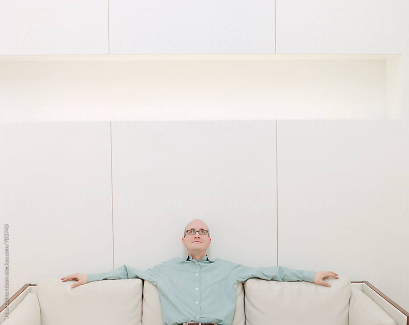 Man relaxing on couch in minimalist, modern hotel lobby by Paul Edmondson for Stocksy United