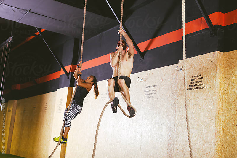 Couple climbing a rope in a gym box.  by BONNINSTUDIO for Stocksy United