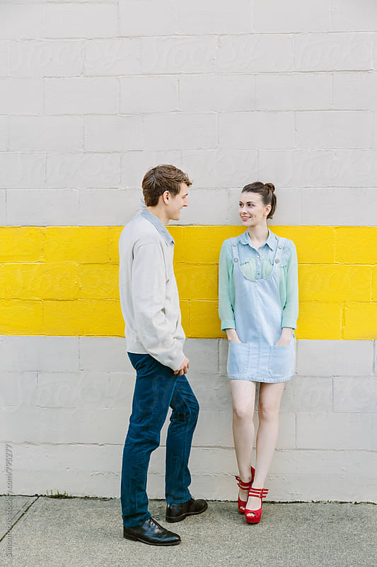 Urban young couple standing against a wall by Simon DesRochers for Stocksy United