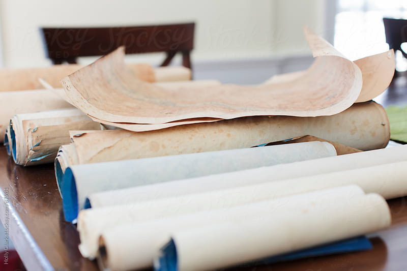 Antique maps and scrolls on a table. by Holly Clark for Stocksy United