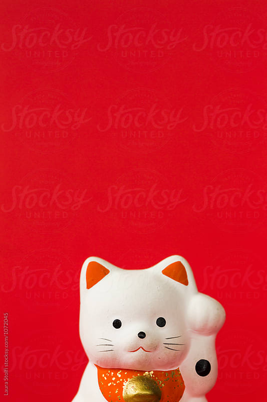 Red porcelain miniature cat beckons on red background by Laura Stolfi for Stocksy United