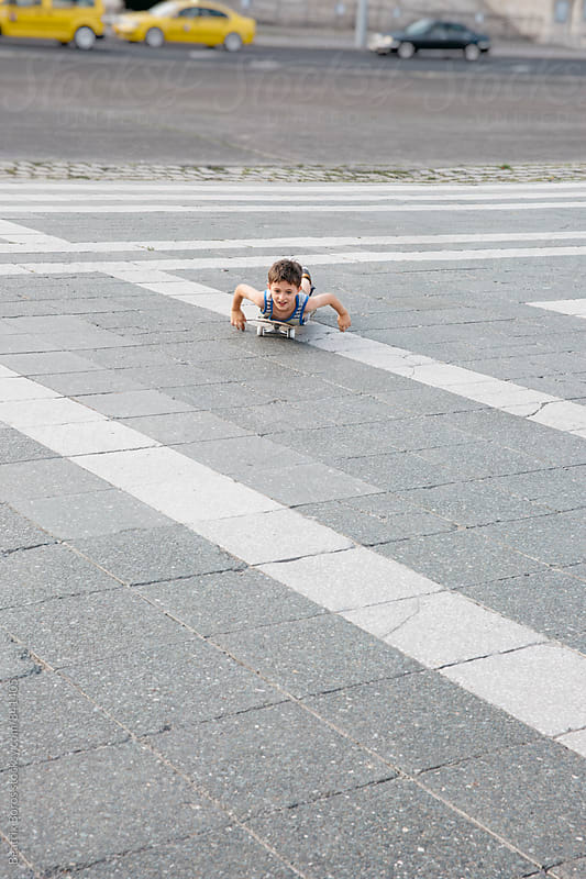 Boy lying on a skateboard in urban area by Beatrix Boros for Stocksy United